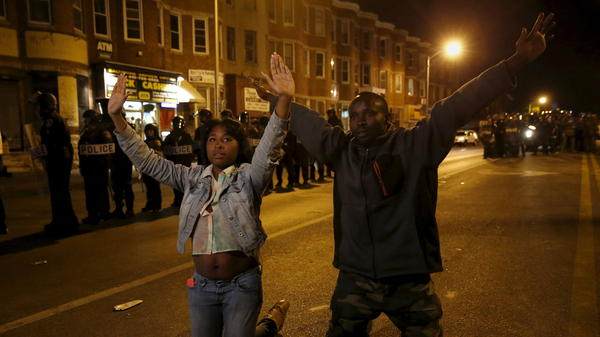 People kneel in front of riot police Wednesday along Pennsylvania Avenue in Baltimore, past the curfew. The two were among the few to defy the curfew as Baltimore remained relatively quiet two days after rioting and looting.