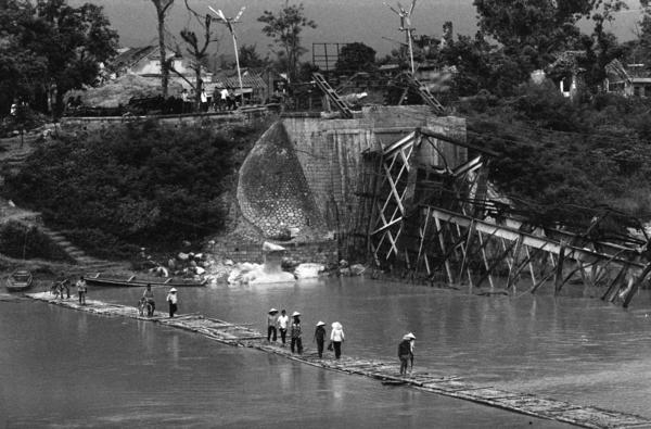 Vietnamese cross the Ky Cuong River on a temporary floating bridge in August 1979. The main bridge was destroyed by the Chinese during a brief border war several months earlier. Vietnam and China have been rivals for centuries and the friction continues to this day.