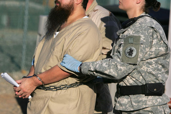 A shackled detainee is transported by guards, including a female soldier, at Camp Delta detention center, Guantanamo Bay U.S. Naval Base, Cuba, in this photo from December 2006.