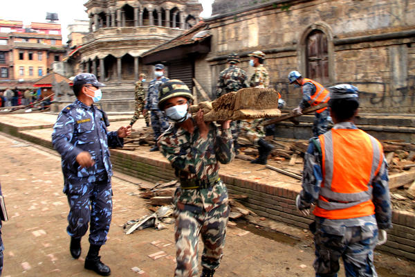 "Uniformed police move wooden beams, stack broken bricks and sift through ruined monuments --€"" some of which date back to the 1600s --€"" in the city of Patan in the aftermath of Nepal's massive earthquake."