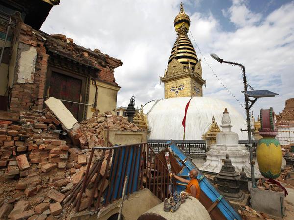 A Buddhist monk picks through a damaged monastery near the Swayambhunath stupa.
