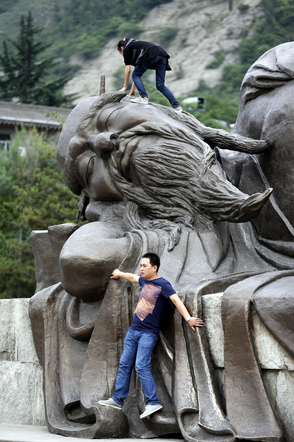 "Not exactly what that's for: Two tourists climb on a statue in Huayin, China, near <a href=""http://www.npr.org/blogs/thesalt/2015/04/21/401253598/tea-tao-and-tourists-china-s-mt-hua-is-three-part-harmony"">Huashan,</a> or Mount Hua, a famed tourist destination, in May 2013."