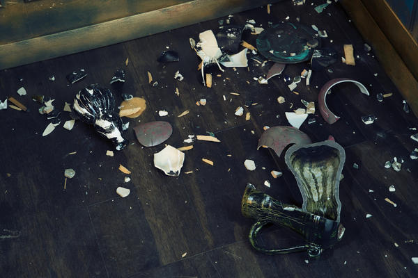 Shards of smashed Asian vases litter the floor of Waterston's <em>Filthy Lucre.</em>