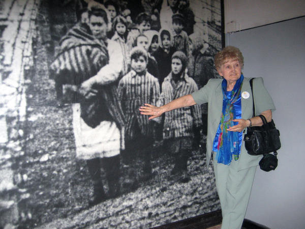 Eva Kor points to an image of herself on the wall of the Auschwitz-Birkenau State Museum in Poland.