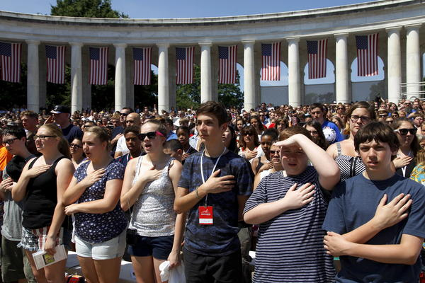 Crowds stand for the national anthem during the Memorial Day observance at Arlington National Cemetery.