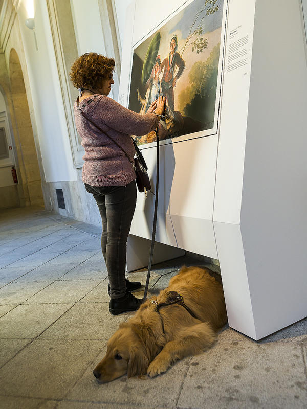 A blind visitor touches a copy of Francisco Goya's 1777 masterpiece, <em>The Parasol</em>.
