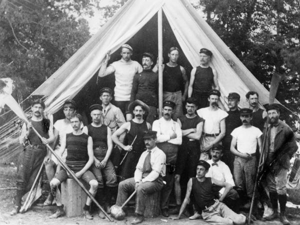 YMCA camp leaders at Camp Dudley in New York. Sumner Dudley, founder of the camp, sits in the center with a mallet.