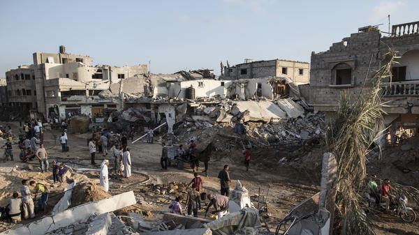 Palestinians walk through an area of destruction on August 15, 2014 in Khuza'a, Gaza. A new report from Amnesty International alleges that during the summer 2014 war between Israel and Hamas, under the cover of conflict, Hamas executed at least 23 Palestinians.