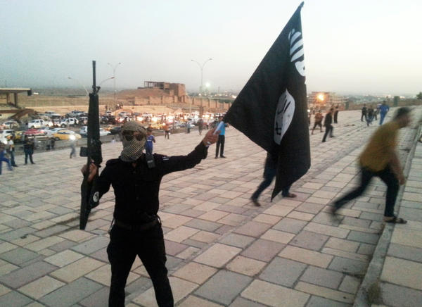 An Islamic State fighter holds holds a rifle and the group's flag shortly after capturing the northern Iraqi city of Mosul in June 2014. Dozens of Americans have been accused of planning or heading off to the Middle East to join the group. Their individual cases are on the chart below.