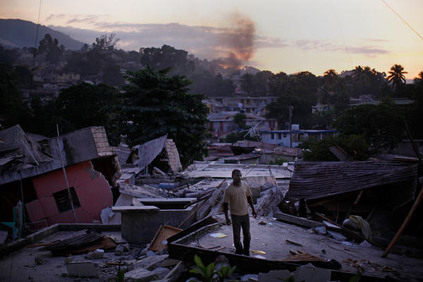 After the quake of 2010, a man stands on a rooftop yelling for any sign of his missing relatives in a Port-au-Prince neighborhood.