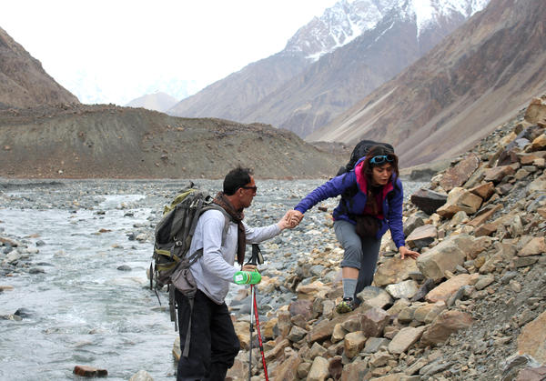 Soheila Hamidi, who is hiking on a taped-up ankle that she sprained a week or so earlier, gets assistance from local guide Malang Darya as they scramble over rocks. Darya is also Hamidi's relative.