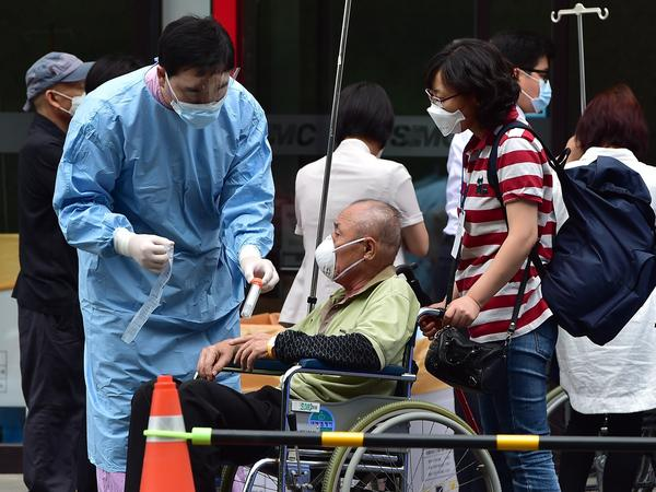 In front of the emergency room at the Samsung Medical Center in Seoul, medical workers care for a man suspected of having the Middle Respiratory syndrome on Monday.