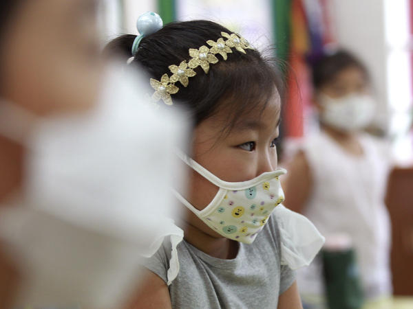 Elementary school students wear masks as a precaution against Middle East respiratory syndrome as they wait for a lesson to start at Midong Elementary School in Seoul on Monday.