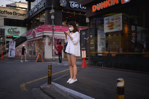 A woman on a street in Seoul checks her cellphone. The government is ramping up efforts to control an outbreak of the Middle East respiratory syndrome by monitoring the smartphones of those under quarantine.