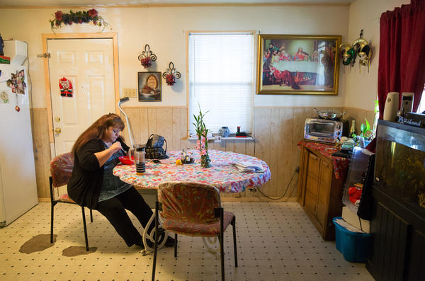 Garcia eats her dinner before attending church on a Wednesday evening. Garcia, who works two jobs, rents a room in her brother's home to save on expenses.