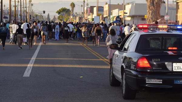 A Los Angeles Police Department car follows protesters as they march near the city's 77th Street police station last August. It was a protest of the fatal LAPD shooting of Ezell Ford.