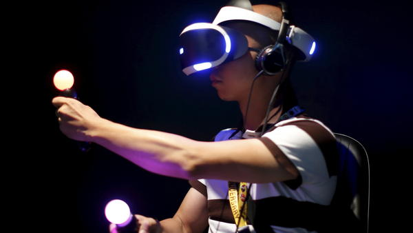 An attendee at the Electronic Entertainment Expo in Los Angeles plays Sony's Project Morpheus London Heist video game with a virtual reality headset and Move controllers.