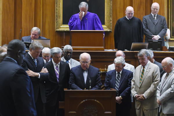 Chaplain James St. John (center) leads state senators in prayer at the Statehouse in Columbia, S.C. State Sen. Clementa Pinckney was one of those killed Wednesday night in a shooting at the Emanuel AME Church in Charleston.