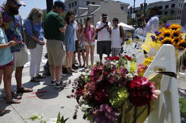 People view flowers on a road leading to the Emanuel AME Church the morning after the shooting in Charleston. Charleston Mayor Joseph Riley said the arrest is a part of the healing process that has just begun.