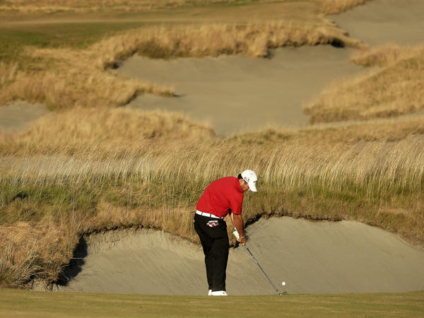 """Patrick Reed hits from the fairway on the 18th hole during the U.S. Open golf tournament at Chambers Bay. Some have criticized the grass's appearance, but others see it as """"the future of the game."""""""