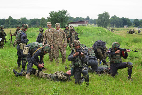 Ukrainian national guardsmen practice protecting and recovering wounded comrades as American military trainers watch.