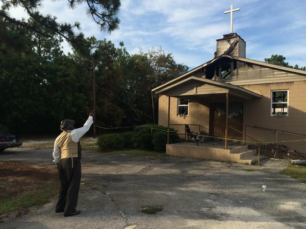 Pastor Bobby Jones points to the cross on top of Glover Grove Baptist Church in Warrenville, S.C., where he has preached for more than 30 years. The steeple was one of the only parts of the church left standing.