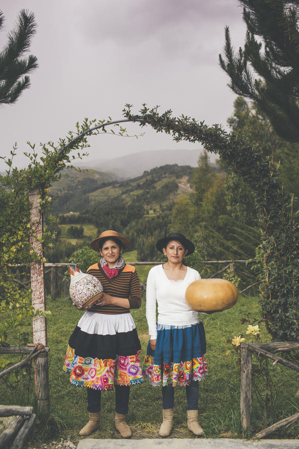 Standing in their backyard in Cochas Grande, Peru, Katya and Blanca Cantos, hold the fruit of their labor. The gourd at left shows scenes from a potato harvest. The just-started gourd at right will tell the story of an ancestor's epic trek.