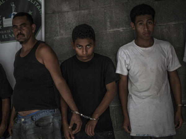 Suspected members of El Salvador's 18th Street gang stand handcuffed in pairs at a police station in Panchimalco, near San Salvador. The government has launched well-publicized raids, roundups and a crackdown on gang leaders, locking them away in maximum security prisons.
