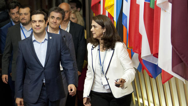 """Greek Prime Minister Alexis Tsipras (front left) leaves after a meeting of eurozone heads of state Monday at the EU Council building in Brussels. The summit reached a tentative agreement with Greece for a bailout program that includes """"serious reforms,"""" removing an immediate threat that Greece could collapse financially and leave the euro."""