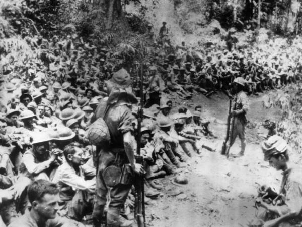 """In this 1942 file photo provided by the U.S. Marine Corps, Japanese soldiers stand guard over American prisoners of war just before the start of the Bataan Death March following the Japanese occupation of the Philippines. Some of those who survived the death march were <a href=""""http://www.nationalmuseum.af.mil/factsheets/factsheet.asp?id=15184"""">later forced to work</a> for Japanese industry."""