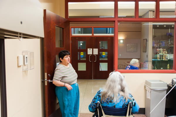 After a class Eagle teaches to the visually impaired on how to use technology, she helps her students navigate their way into the hall. In addition to her volunteer work, Eagle plays piano at the center.