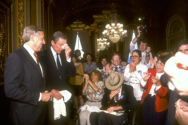 Congressman Steny Hoyer, D-Md., and Sen. Orrin Hatch, R-Utah, are applauded after Congress passed the Americans with Disabilities Act. President George H. W. Bush signed the act into law on July 26, 1990.