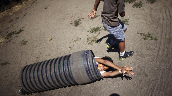 Ten-year-old Deion Jefferson and 7-year-old Samuel Jefferson push and roll a piece of culvert piping down a hill.