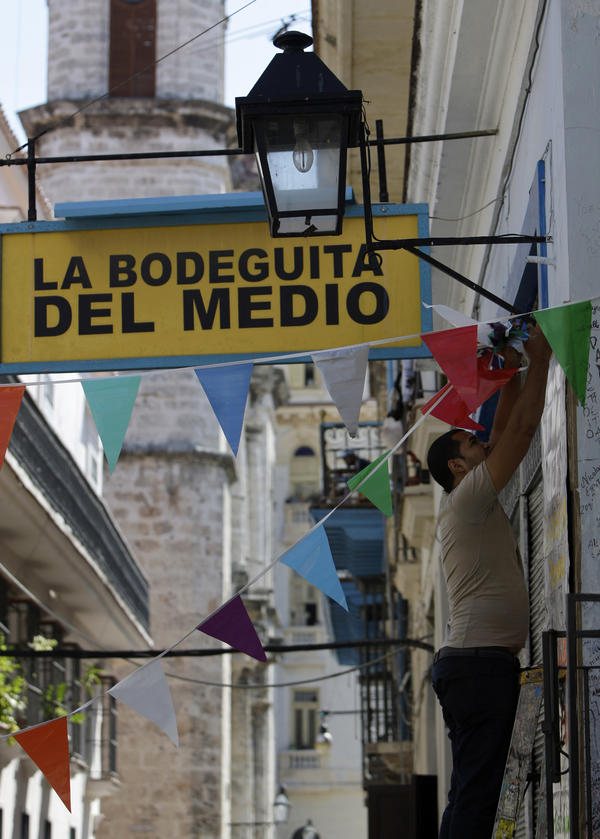 A worker hangs decorative flags outside La Bodeguita del Medio in Old Havana. The restaurant celebrated its 70th anniversary on Thursday.