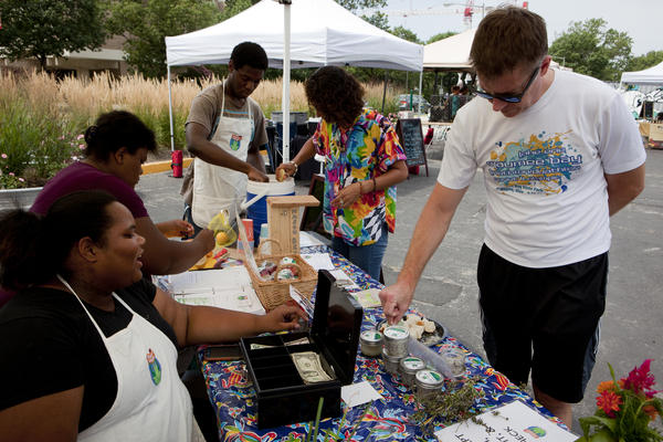 Roshawn Little (left) invites customer Nate Kohring to try the herbed salt with bread at the Aya farmers market on Saturday.