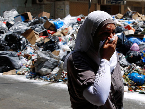 A Lebanese woman covers her nose as she walks past piles of garbage on a Beirut street.