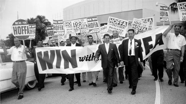 Jimmy Hoffa (walking at left in front) leads a parade of supporting delegates to the Teamsters Union Convention in Miami Beach in 1957.