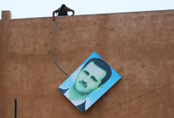 A fighter with Jabhat al-Nusra, the al-Qaida affiliate in Syria, takes down a picture of Syria's President Bashar Assad in the northwestern city of Ariha in May. Jabhat al-Nusra is strong in this area, and recently captured Syrian fighters trained by the U.S.