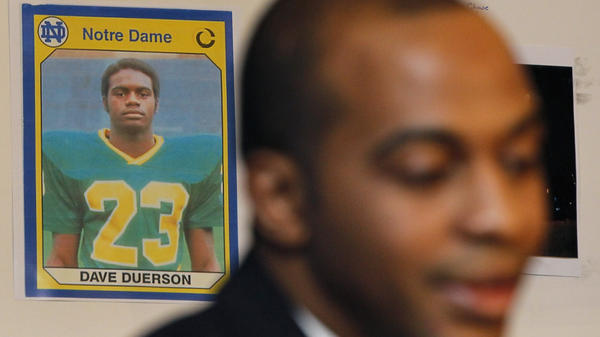 A photo of former Chicago Bears Dave Duerson, while he was playing at Notre Dame, hangs behind his son Tregg as Tregg announces a wrongful death lawsuit against the NFL in 2012.