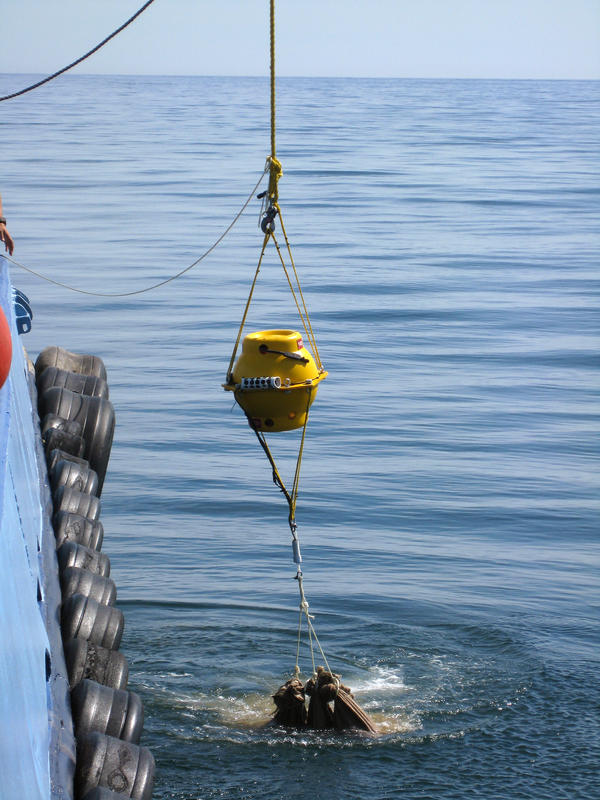 Underwater acoustic recording units being dropped with sandbags into Massachusetts Bay. These recorders are housed in a pressurized glass sphere and have been successfully deployed around the world, from tropical waters to the polar seas.
