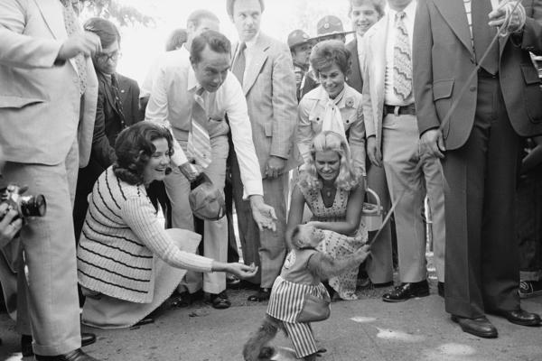 Then-vice presidential candidate Sen. Robert Dole (bending down) and his wife, Elizabeth, gave coins to a monkey at the Iowa State Fair in 1976.