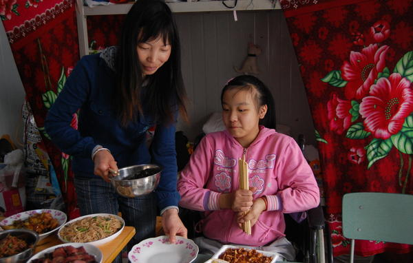 Meihua and her parents shared a room at a temporary school following the earthquake. She's shown here with her mother in 2009, a year after the quake.