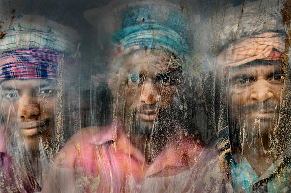 <strong>Second Place:</strong> Three gravel workmen look through a window at their workplace in Chittagong, Bangladesh. Dust and sand are everywhere.