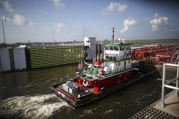 A tug and barge pass through the open flood gates at the 1.8-mile-long Lake Borgne Surge Barrier, which is part of the Southeast Louisiana Flood Protection Authority.