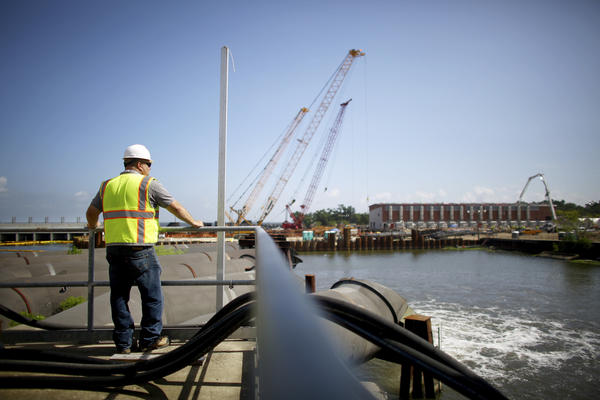 A maintenance worker watches water pour out of the temporary outflow pipes at the pumping station for the 17th Street Canal in the Orleans Levee District. The new and permanent pump house is still under construction in the distance.
