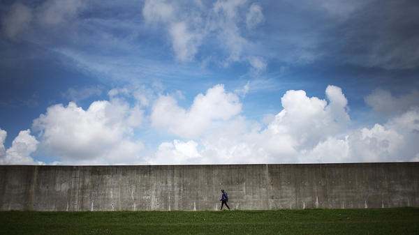 A woman walks along the rebuilt Industrial Canal levee wall in New Orleans' Lower Ninth Ward on May 18.