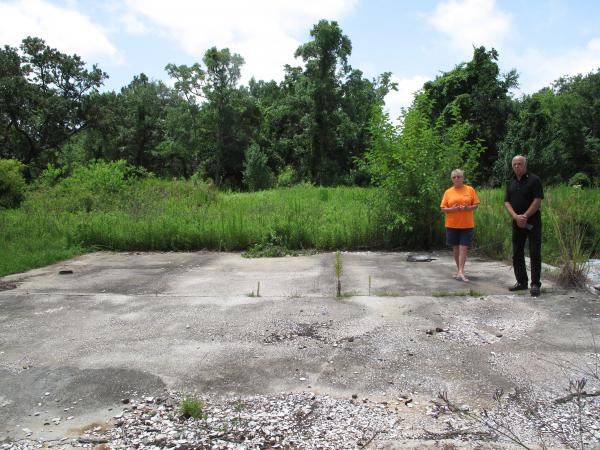 Stephanie Nelson Bosarge and her brother Paul Nelson show what's left of the family's oyster processing shop. The raised concrete slab is what's left of the oyster run.