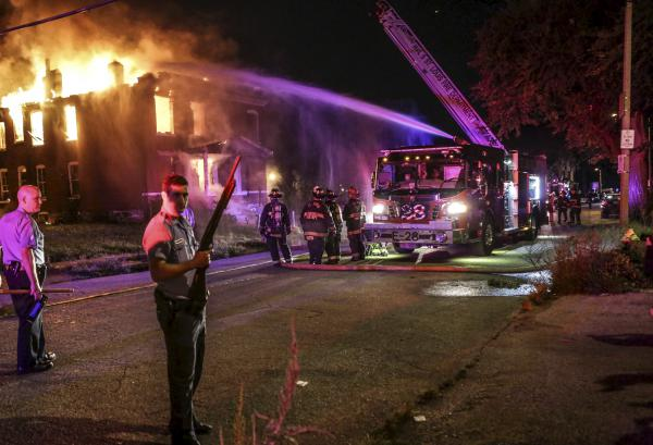 Firefighters attempt to put out a fire at an abandoned building with the protection of St. Louis City Police in St. Louis, on Thursday.