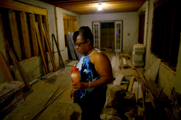 Angela Chalk walks through the still-unfinished ground floor of her home in the 7th Ward of New Orleans. Her current residence sits atop the old house, which is part of the new code for property owners who are rebuilding.