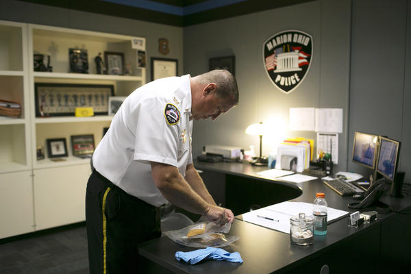 Police Chief Bill Collins inspects confiscated crack cocaine and brown powder heroin in Marion.